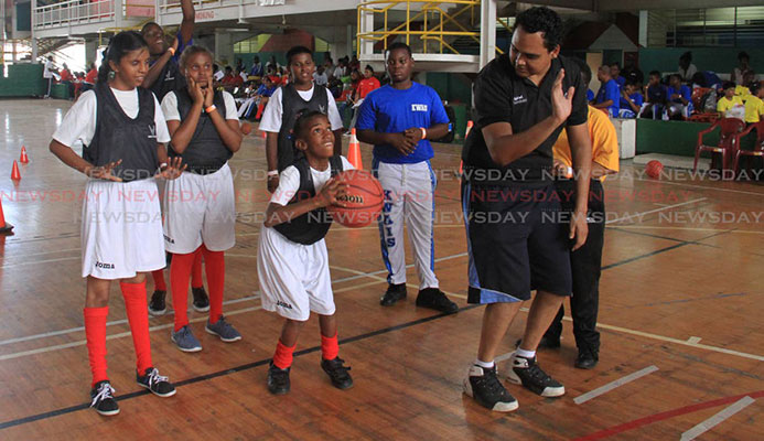 Nigel Clarke, right, shows Rayanna Flanders how to shoot during a basketball drill at the Special Olympics National Games, held at the Jean Pierre Complex, yesterday.
