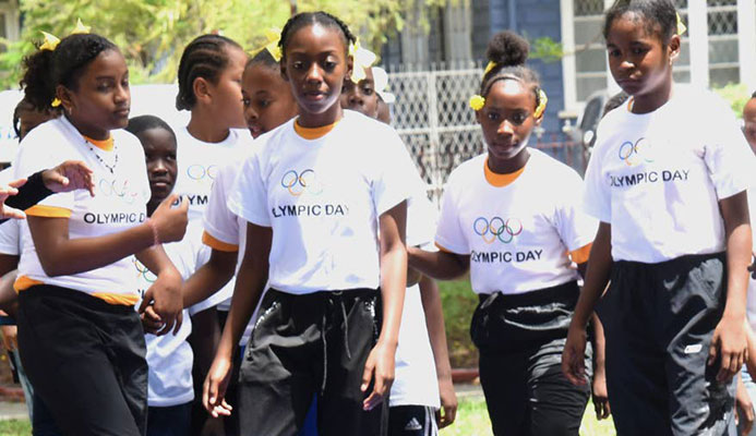 A young gymnast has the attention of other children at Olympic Day 2019 at Lord Harris Square, Port of Spain, on Friday. PHOTOS BY KERWIN PIERRE
