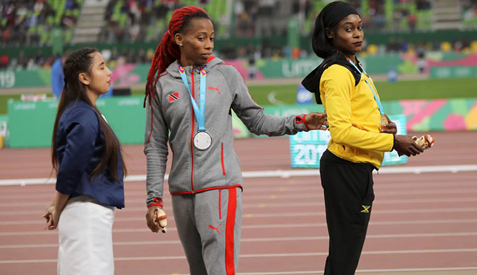 Gold medallist Elaine Thompson of Jamaica (right) and silver medallist Michelle-Lee Ahye of TT stand on the podium for the women's 100m at the Pan American Games in Lima, Peru on Wednesday.