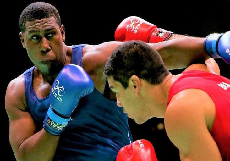 COMPLYING WITH PANDEMIC RESTRICTIONS: Trinidad and Tobago super-heavyweight Nigel Paul, left, seen in action, is awaiting word of a new date for Olympic qualifying for the Americas.